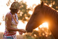 Beautiful girl feeding her handsome horse and a senior portrait taken during sunset Royalty Free Stock Image