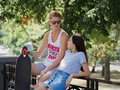 A beautiful girl and a fellow talking on a bench, a cute couple of teens dating in a park, on a natural blurred Royalty Free Stock Photo