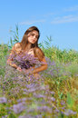 The beautiful girl is in the field covered with flowers a bouquet of wild Stock Image