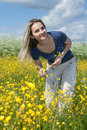 Beautiful girl in field with yellow flower Royalty Free Stock Photo
