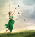 Beautiful girl following butterflies on a mountain in green dress Stock Photos