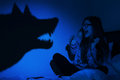 Beautiful girl frightened from wolf shadow at wall in bedroom Stock Photo