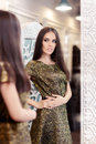 Beautiful girl in golden brocade dress looking in the mirror portrait of a young woman a dressing room wearing new gown Stock Images