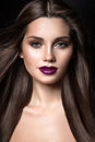Beautiful girl with golden makeup and burgundy lips with the wind in hair beauty face picture taken studio on a black Stock Images