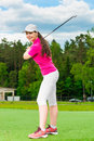 Beautiful girl on a green lawn with a golf club posing Royalty Free Stock Images