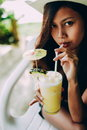 Beautiful girl with the hat, drinking fresh and refreshing pineapple juice, summer holiday vacation