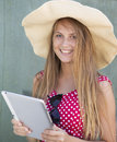 Beautiful girl in hat holding tablet computer in hand years old woman over the green wall background outdoors daylight Stock Photos