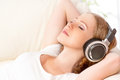 Beautiful girl in headphones enjoying music at home on the couch Royalty Free Stock Photos