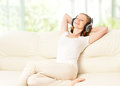 Beautiful girl in headphones enjoying music at home on the couch Stock Photo