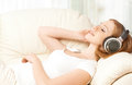 Beautiful girl in headphones enjoying music at home on the couch Stock Image