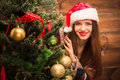 Beautiful girl hiding behind a New Year tree Royalty Free Stock Photo