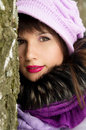 Beautiful girl hiding behind tree nature winter Stock Photo