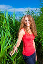 Beautiful girl among high grass of meadow Stock Image