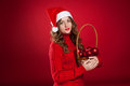 Beautiful girl holding basket with christmas tree decorations brunette curly hair wearing santa claus hat Royalty Free Stock Photos
