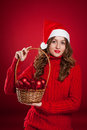 Beautiful girl holding basket with christmas tree decorations brunette curly hair wearing santa claus hat Royalty Free Stock Images