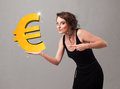 Beautiful girl holding a big d gold euro sign young Royalty Free Stock Image