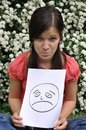 Beautiful girl holding a paper with a drawn face e Royalty Free Stock Photography