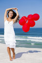 Beautiful girl holding red ballons with in the beach Royalty Free Stock Image