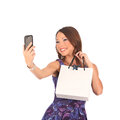 Beautiful girl holding shopping bags and taking selfie with cell phone isolated on white Royalty Free Stock Photo
