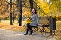 Beautiful girl horizontal photo sit on bench in autumnal park Royalty Free Stock Image