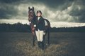 Beautiful girl with horse standing near outdoors against moody sky Royalty Free Stock Photos