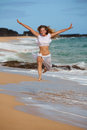 Beautiful Girl Jumping on the Beach Royalty Free Stock Images