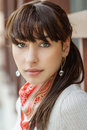 Beautiful girl with kerchief on neck against wooden handrail Royalty Free Stock Images