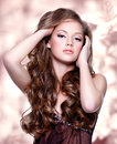 Beautiful girl with long curly hairs over art background Royalty Free Stock Images