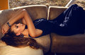 Beautiful girl with long hair in elegant dress lying on divan Royalty Free Stock Photo