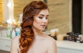 Beautiful girl, with long, red-haired hairy. Hairdresser weaves a French braid, close-up in a beauty salon Royalty Free Stock Photo