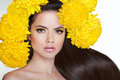 Beautiful girl with long shiny straight brown hair styling. Young attractive woman with flowers on head. Royalty Free Stock Photo