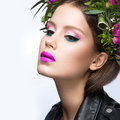 Beautiful girl with a lot of flowers in their hair and bright pink make-up. Spring image. Beauty face. Royalty Free Stock Photo