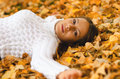 Beautiful girl lying on the autumn leaves in forest Royalty Free Stock Photos