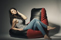 Beautiful girl lying on beanbag brunette bean bag Royalty Free Stock Images