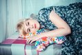 Beautiful girl lying down and hugging a cushion with buterffly shape Royalty Free Stock Photography
