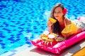 Beautiful girl lying on an inflatable pink mattress eating tropical fruits mango, dragon fruit, papaya and pineapple on