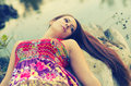 Beautiful girl lying on the tree trunk of fallen Stock Photography