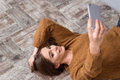 Beautiful girl lying on wooden floor and making selfie Royalty Free Stock Photo
