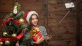 Beautiful girl making selfies near New Year tree Royalty Free Stock Photo
