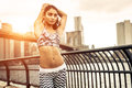 Beautiful girl making stretching before intense running in new york city walkway with brooklyn bridgeand skyline the background Royalty Free Stock Image
