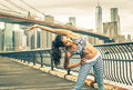 Beautiful girl making stretching before intense running in new york city walkway with brooklyn bridgeand skyline the background Royalty Free Stock Photography
