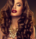 Beautiful girl model with long brown curled hair large necklace Stock Image