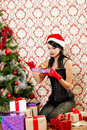 Beautiful girl near a christmas tree with gifts in hand Royalty Free Stock Photo