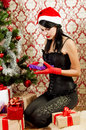 Beautiful girl near a christmas tree with gifts in hand Stock Photography