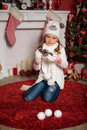 Beautiful girl near christmas tree sitting on a carpet and holding pine cones in hands Royalty Free Stock Photography