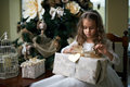 Beautiful girl near Christmas tree unpacking presents Royalty Free Stock Photo