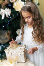 Beautiful girl opens   gift for the new year Royalty Free Stock Photo