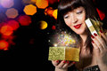 Beautiful girl opens a gift in small box golden festive night holiday Royalty Free Stock Photography