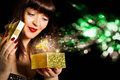 Beautiful girl opens a gift in small box golden festive night holiday Stock Image