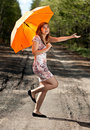 Beautiful girl with an orange umbrella Royalty Free Stock Photos